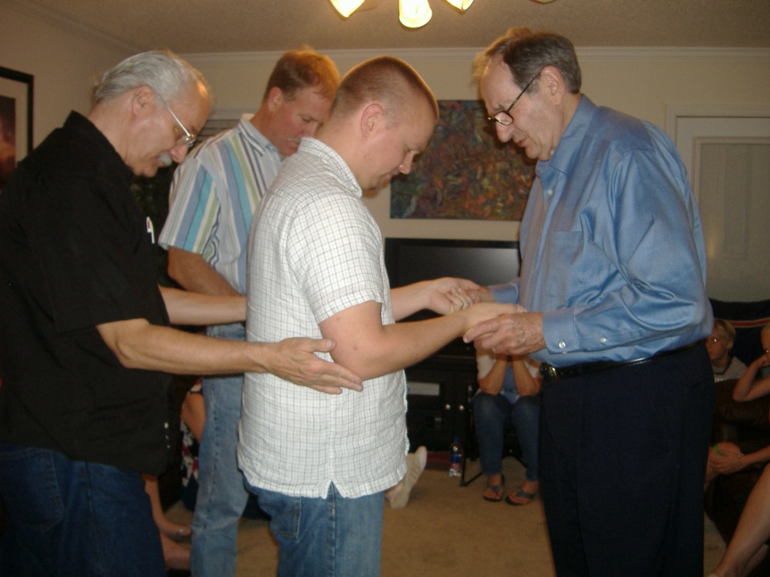 Joel receiving ministry from Wade Taylor who ordained him and his wife, Lauren, in 2001